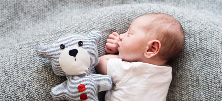 Newborn Baby Boy Lying On Bed With Teddy Bear, Sleeping