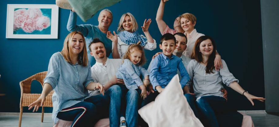 Grandparents, Parents And Their Little Children Sit Together On
