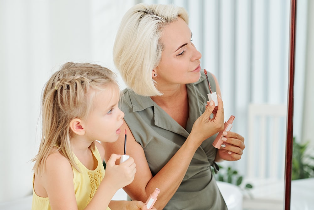 mother and daughter applying lipstick